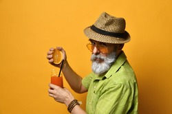 Gray-bearded aged male in hat, green shirt, sunglasses. He squeezes an orange into a glass of fresh juice with slice of lemon and tube, posing sideways on orange background. Close up, copy space