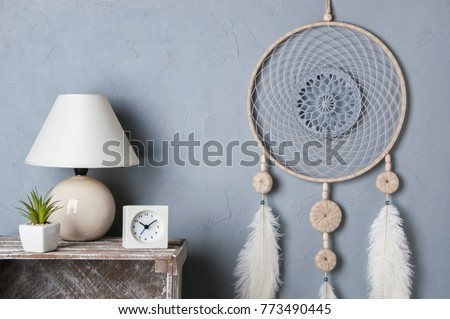 Gray beige dream catcher in bedroom interior on gray textured background. Bedroom decor