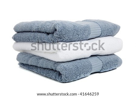 Gray blue and white towels with a white bar of soap on a white background