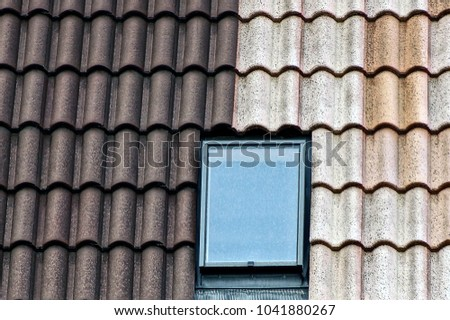 Gray brown tiles and a glass window on the roof of the building