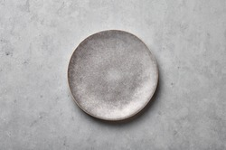 Gray ceramic plate on grey concrete rough background. Empty spotted uneven saucer. Matte dish on stone textured backdrop. Hand made ceramic table setting. Top view