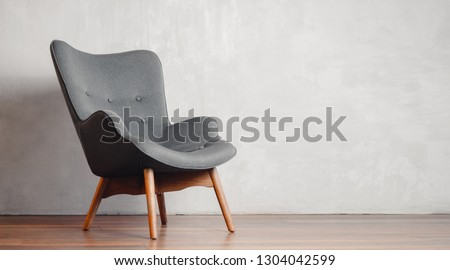 Photo of  Gray chair in white concrete room for copy space. Concept of minimalism.