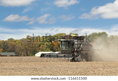 Gray combine harvesting a crop of soybeans