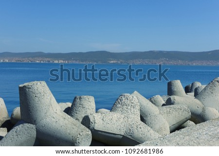 Gray concrete breakwaters against blue sea and sky close-up #1092681986