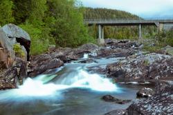 Gray concrete bridge across a clean blue river in Norway
