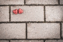 Gray concrete tiles on the floor and two red hearts. background for valentine's day postcard. space for text, space for copy, flat barking