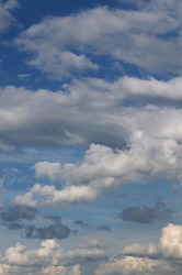 Gray cumulus clouds at their zenith, illuminated by the sun, golden over the horizon, dark blue rain between them. Sky with a blue gradient. Summer evening sky. Background image. Vertical photo.