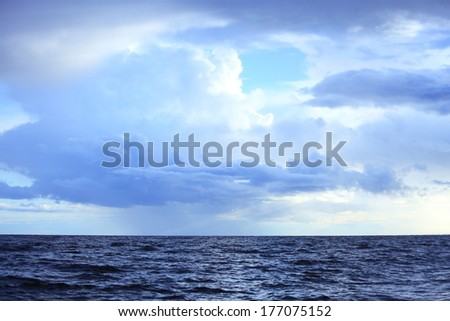 Gray deep blue fluffy thunder clouds stormy sky above a dark surface of the sea. Meteorology