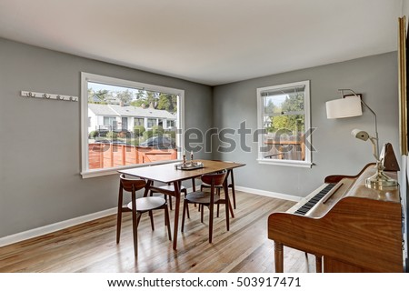 Photo of Gray dining room interior with piano and wooden table and four chairs. Northwest, USA