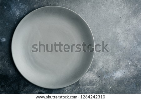 Gray empty plate (ceramic) on a gray stone background. Gray minimalism concept. Copy space.