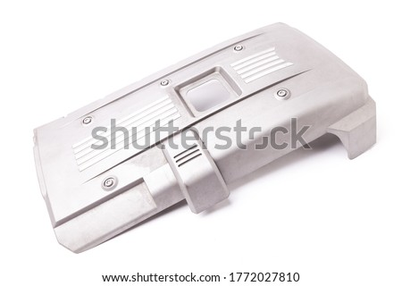 Gray engine cover on a white background in a photo studio as a separate spare part for sale at an auto-parsing or for replacement when repairing a car in the service.