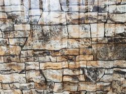 Gray facade facing tiles, imitating a stone. Background texture.