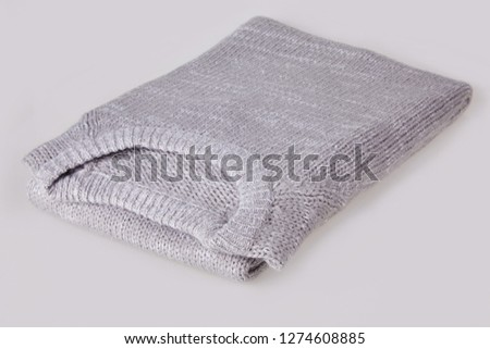 Gray folded knitted sweater with blank tag on white background. Clothes, fashion concept. Long sleeve tunic #1274608885