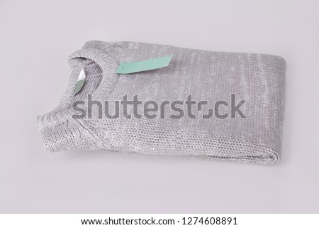 Gray folded knitted sweater with blank tag on white background. Clothes, fashion concept. Long sleeve tunic #1274608891