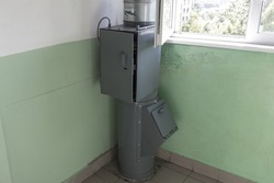 gray garbage chute in a multi-storey residential building on the top floor