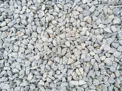 Gray gravel background with copy space. The natural texture of grey stones. Rough stone background. Grunge backdrop with textured pebbles.