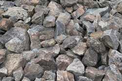 Gray gravel stones for the construction industry. Large Pile of Grey Boulder Rocks. Stone background, dark gravel pebbles stone texture, granite.