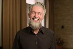 gray-haired bearded adult male smiling and showing positive disposition