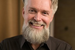 gray-haired bearded adult male smiling and showing positive disposition, close up