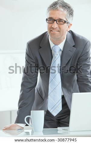 Gray haired businessman using laptop computer, standing behind office desk, working.