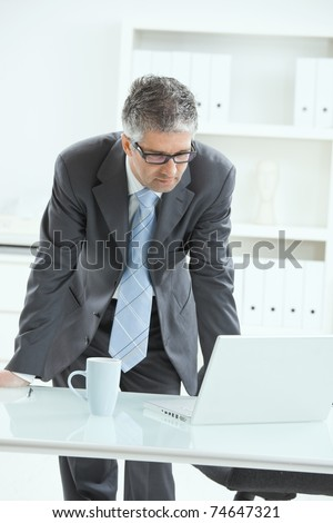 Gray haired businessman using laptop computer, standing behind office desk, working. ?