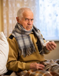 gray haired elderly man measuring pressure with tonometer at home