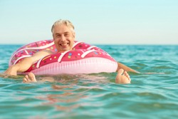 Gray-haired funny man swims on an inflatable circle in the sea