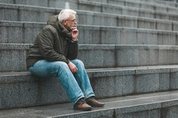 Gray-haired man is lost in thought and sits on the steps. Nostalgia for a pensioner.