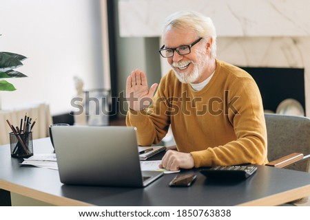Gray-haired mature man communicating on video conference with colleagues waving hand to them and smiling while sitting at his workplace at home