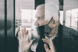 gray-haired old man, forced to remain in quarantine due to the covid-19 coronavirus, looks out the window with a disconsolate expression. Loneliness of old people. Stay home in the pandemic