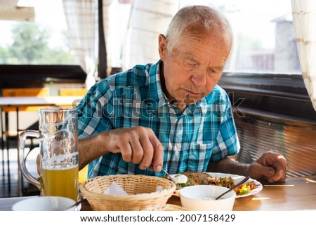gray haired señor dines on the terrace restaurant in the afternoon Foto stock ©
