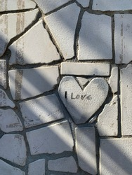 gray heart shaped tiles on the wall with love lettering. romance is everywhere.love confession on wall tiles.