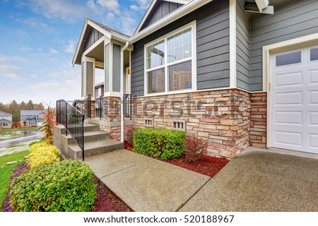 Gray house exterior with column porch and stone wall trim on a rainy day. Northwest, USA