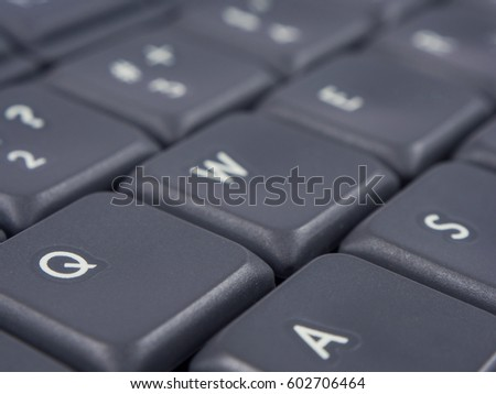 Gray keyboard with focus on q and a buttons and soft focus on back