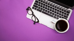 gray laptop with a cup of coffee and glasses on purple background table, working place at home or in the office