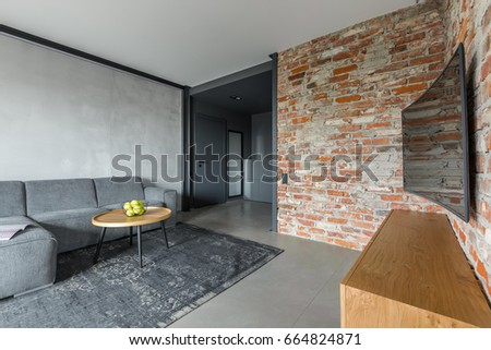 Gray living room with sofa, table, curved tv and industrial brick wall