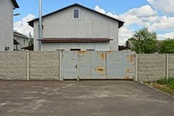 gray metal gate and concrete fence on the pavement in front of a private house with a window against the sky and clouds