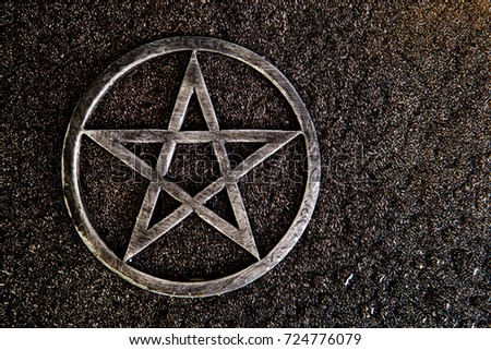 Gray metal pentagram on slate background with water drops - with copy space