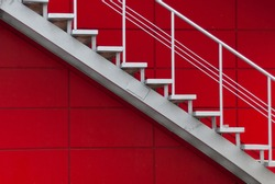 gray metal stair on the red wall. minimalism concept