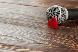 Gray microphone on dark wooden background. Microphone with red heart and copy space. Valentines Day concept.