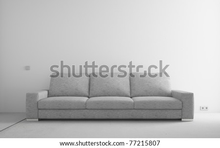 Gray modern sofa in empty room with white walls and concrete floor