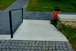 gray monolithic concrete park bench made of concrete in the shape of round stones wooden staircase bench with staircase lighting with metal railing black lattice on the stairs, wheelchair ramp