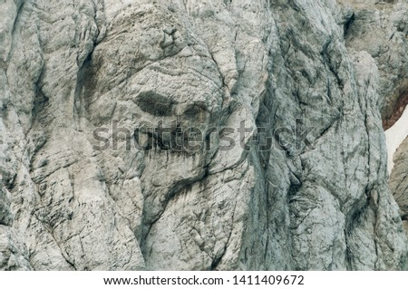 Gray mountain wall resembling a pirate skull face in Slovenian Alps. Alpinism, mountain climbing, traversing, natural features and symbolism concepts