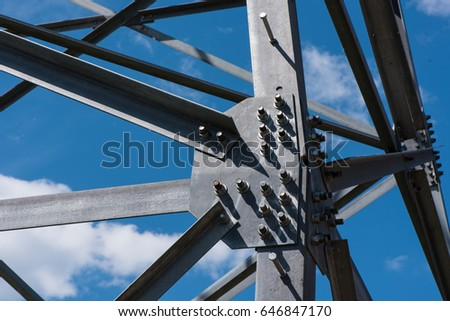 Gray painted metal bolts and rivets on high frame construction on blue sky background with white clouds