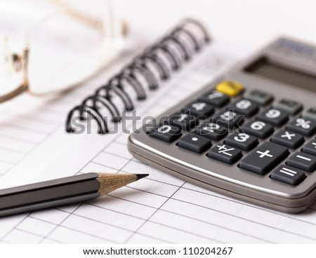 Gray pencil, glasses and calculator on notebook