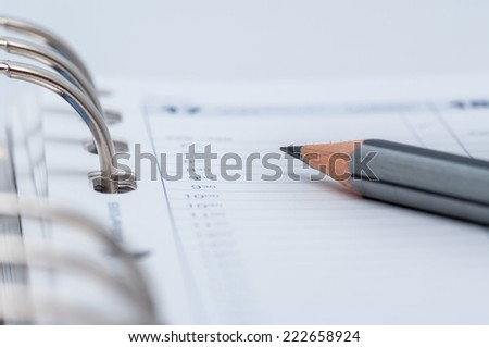 gray pencil on open business agenda, shallow DOF