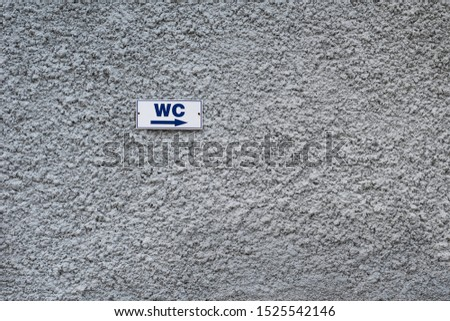 Gray plastered wall and toilet sign, patterned background, indented protruding texture  Stok fotoğraf ©