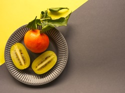 Gray plate with yellow sliced kiwi and orange with green leaves on yellow and gray background. Illuminating und ultimate gray, color trend 2021. Creative tropic fruit concept. Minimalism aesthetic.