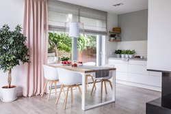 Gray roman shades and a pink curtain on big, glass windows in a modern kitchen and dining room interior with a wooden table and white chairs