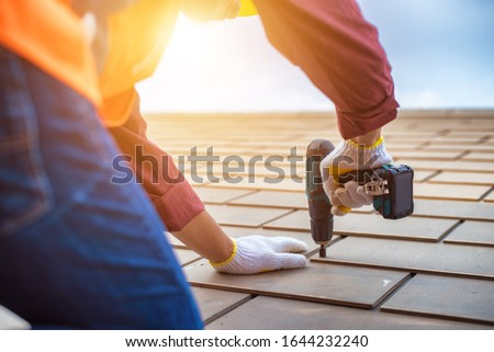 Gray roof - Repair and Replace the House Roof with Handyman with Tools and Pprotective equipment. Stand on the Roof with the Ssky Background. Stock photo ©